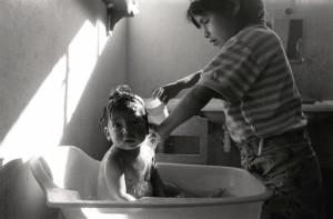 Julia baña a su hermanito, porque no hay nadie quién más lo haga, al menos con el amor con que lo hace...